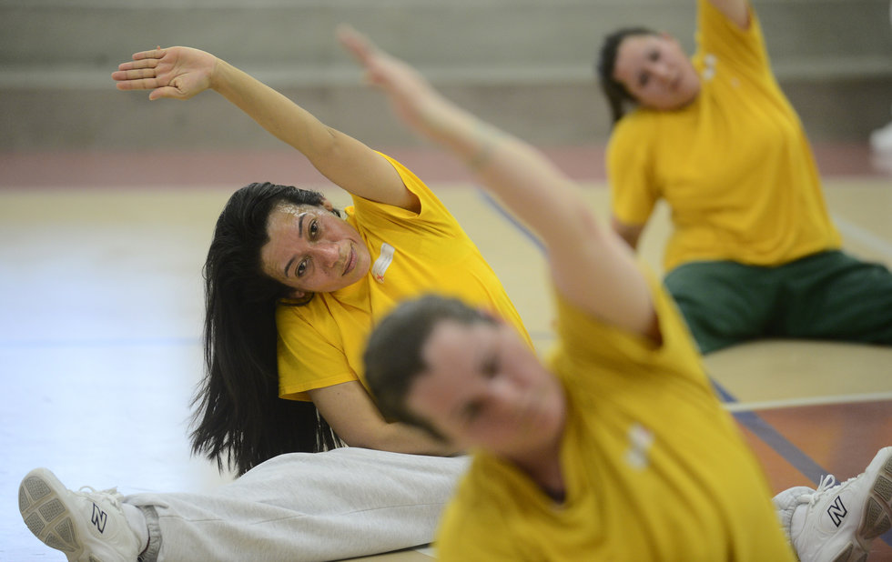 A group of women in prison, wearing yellow T-shirts and gray sweatpants, are stretching on a gym floor in a straddle split with one arm reaching to the side.