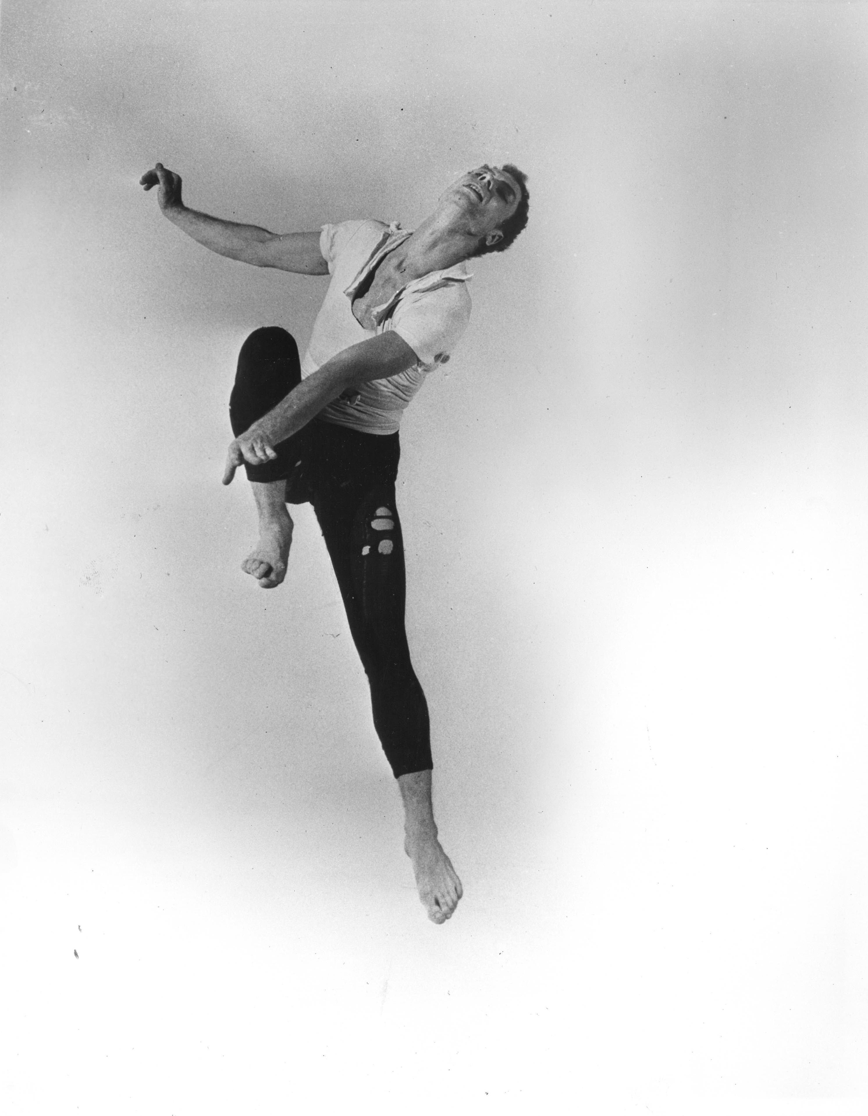 A young Merce Cunningham, dressed in hole-filled rehearsal-wear, jumps, one knee raised to his chest, head flung back.