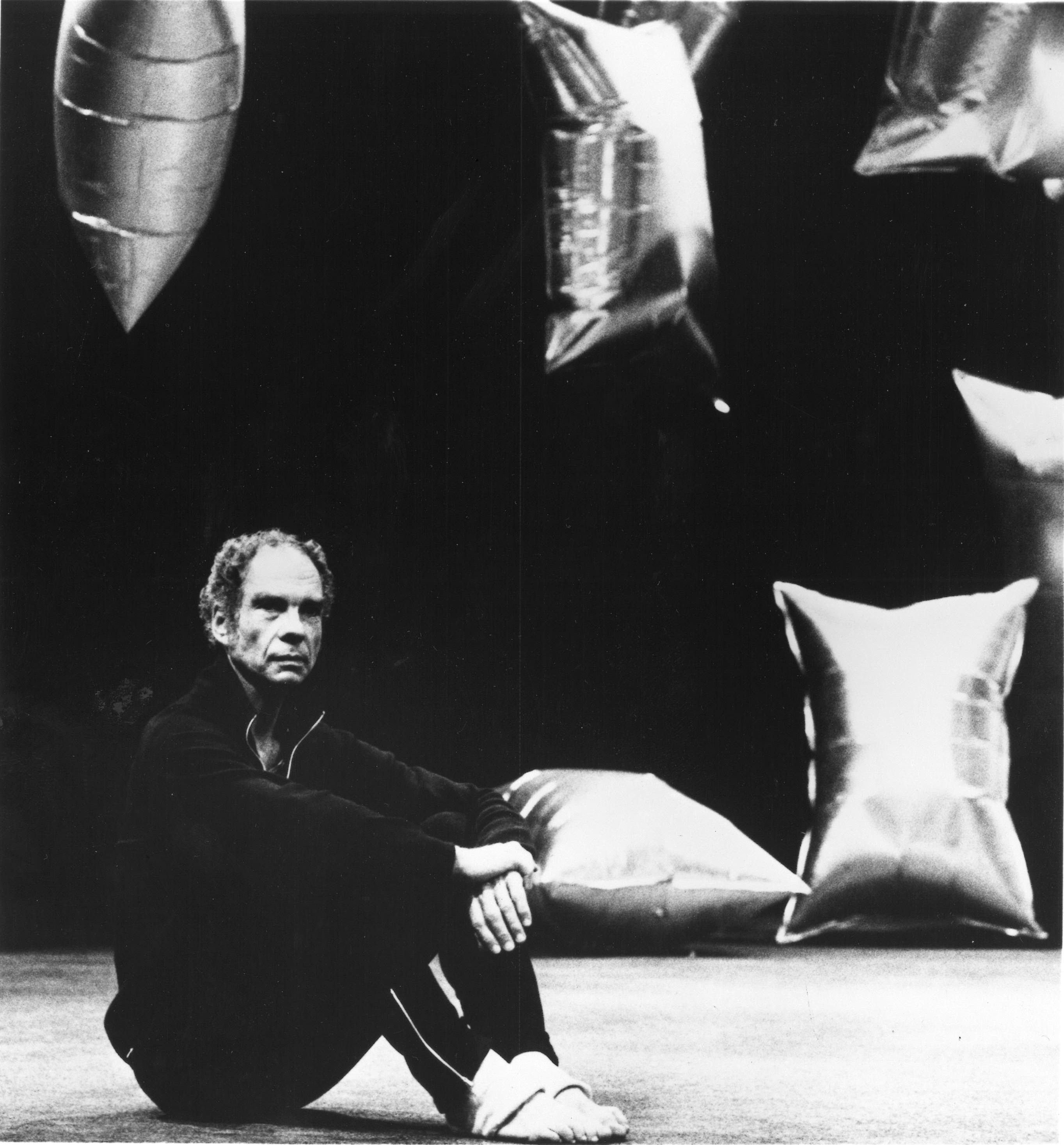 Merce Cunningham, in a black tracksuit, sits with his knees pulled up onstage. Behind him, the silver balloons designed by Andy Warhol for Cunningham's RainForest.