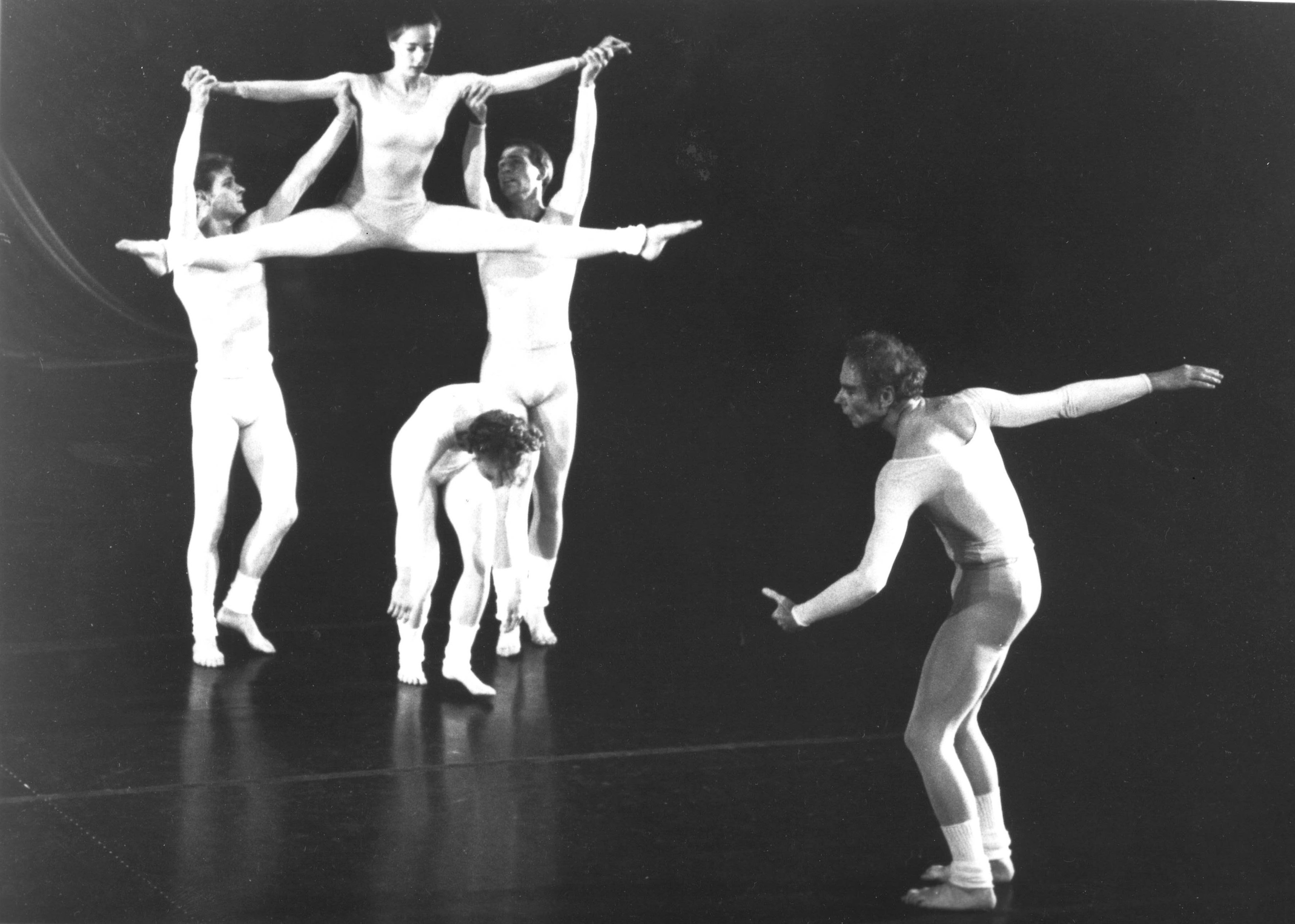 Two male dancers list a woman, legs split, over a third, who is crouching. Merce Cunningham gestures with an arm behind him in the corner. All wear pale unitards and legwarmers.