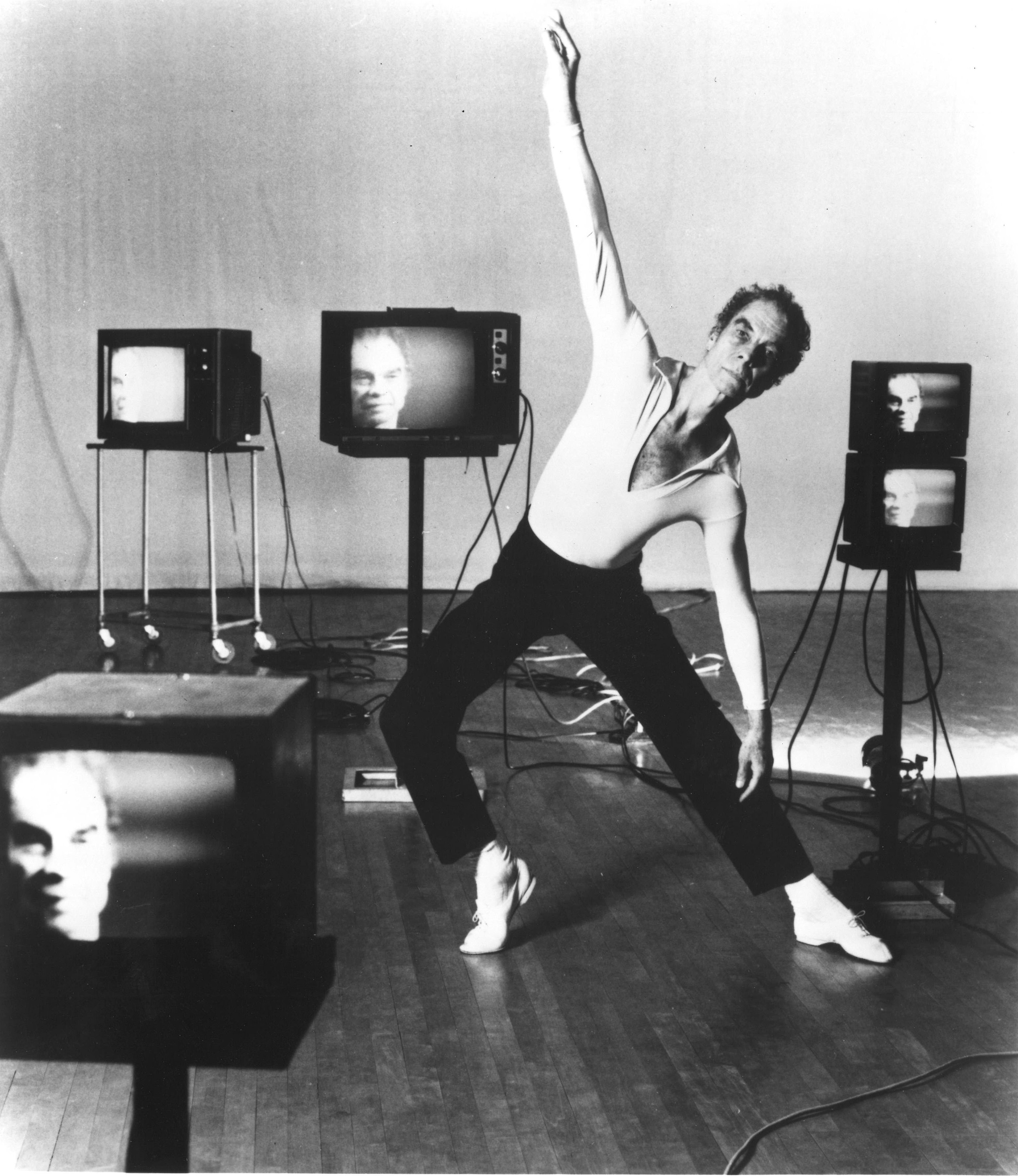 Five small, square television sets of various sizes show a blurry image of Merce Cunningham's face. Cunningham himself is in the middle of the seemingly random array, holding a side lunge with his right arm raised and right foot in forced arch.