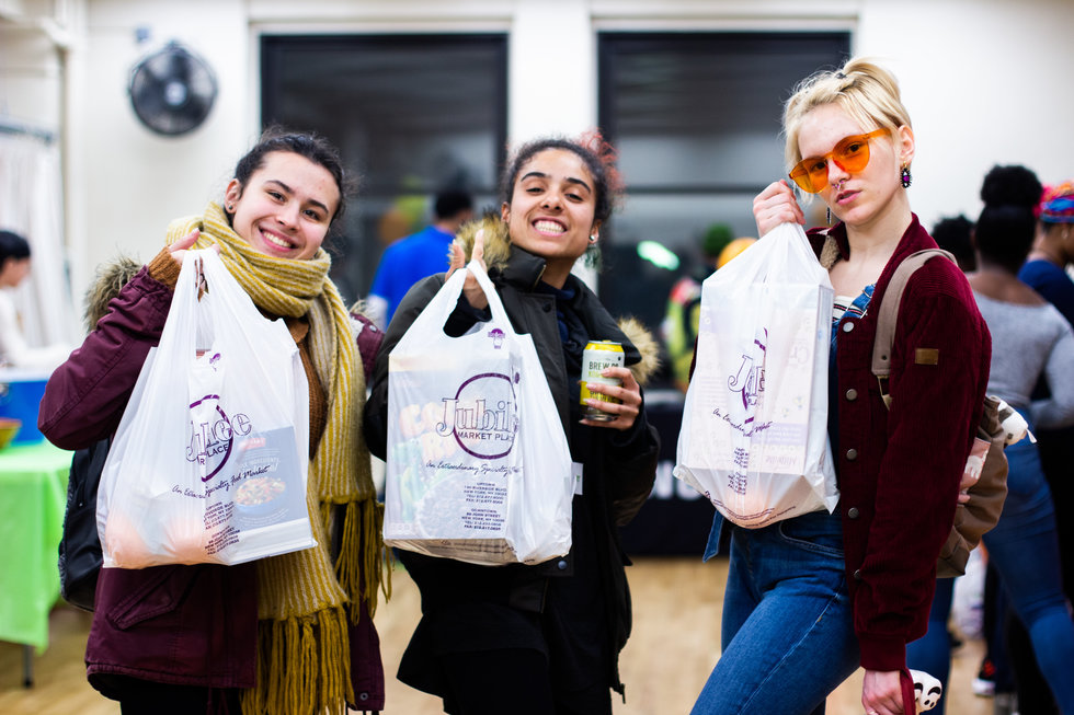 Three young women hold up bags of groceries, smiling.