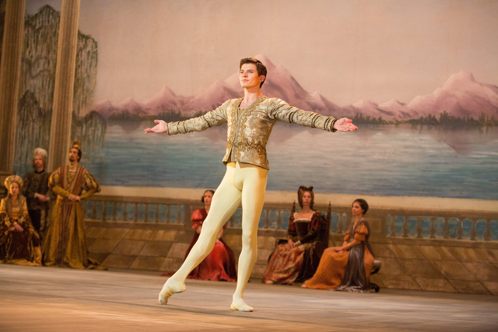 In The White Crow, Rudolf Nureyev, costumed in a gold costume and tights, prepares to turn during a performance.