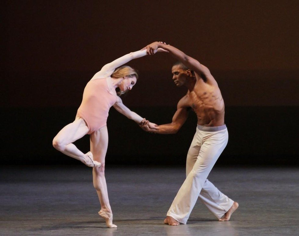 Wendy Whelan in pass\u00e9 wearing just a pale pink leotard holds the hands of Craig Hall and leans away