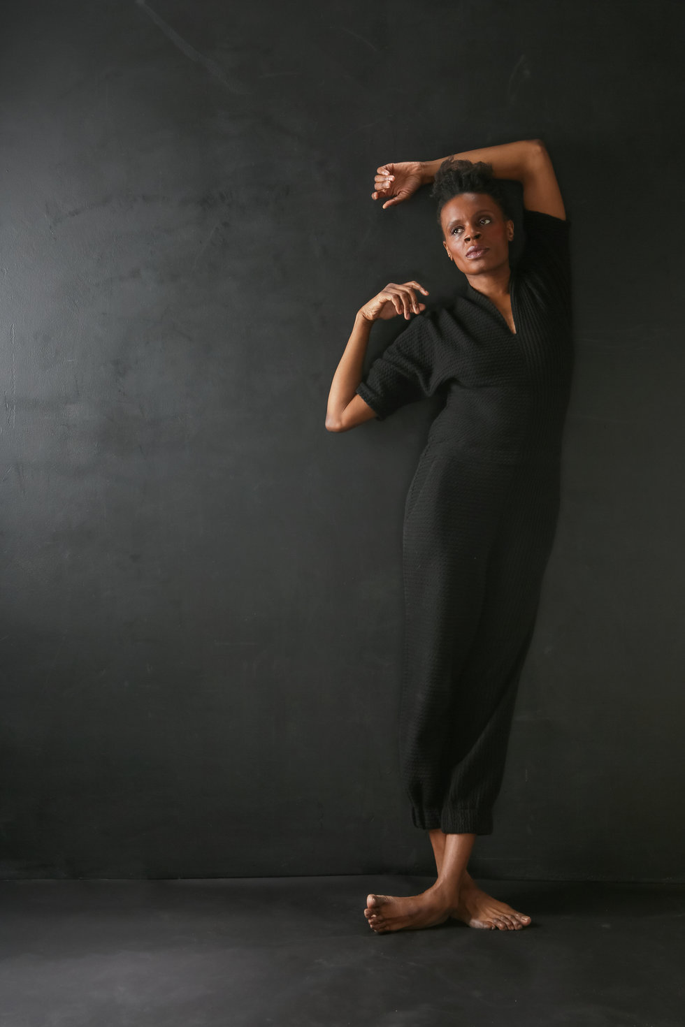 Okwui Okpokwasili leans against a dark background, one foot crossed over the other