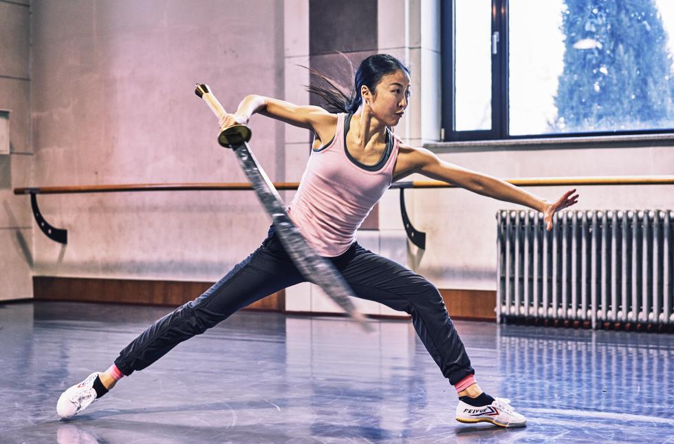 PeiJu Chien-Pott wields a sword in a wide lunge