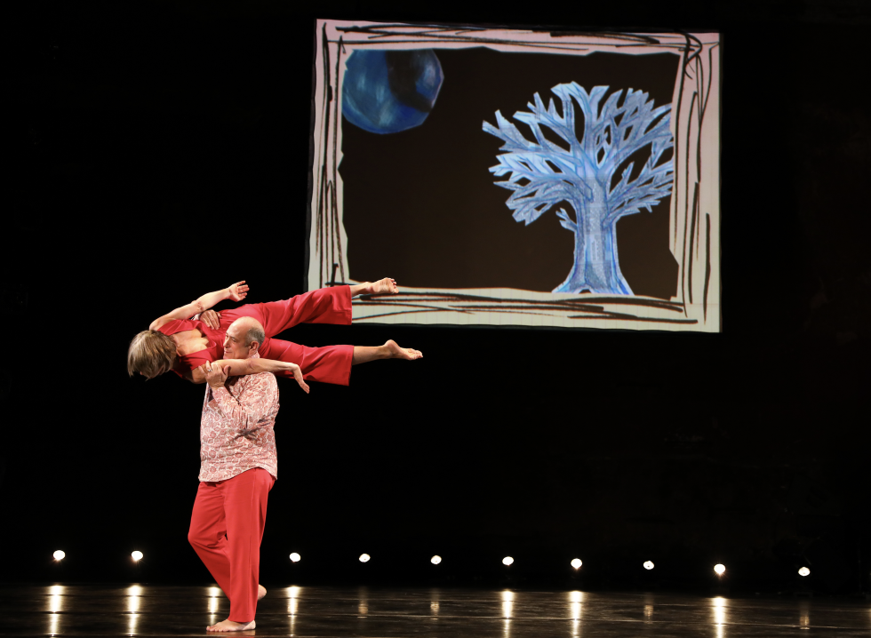 David Dorfman walks across a stage carrying a woman on his shoulders