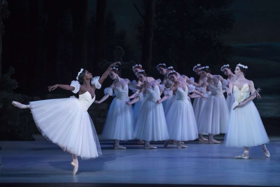 Murphy as Myrtha in Giselle. She is in arabesque, with the rest of the willis in formation behind her, gesturing towards her with a subtle port de bras.