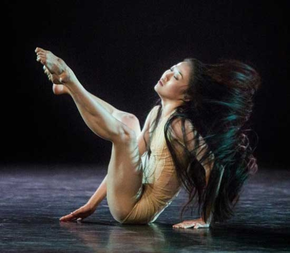 PeiJu Chien-Pott in a Graham contraction while sitting on the ground, her legs extended up in the air with bent knees. She wears a tan leotard and her black hair is down and flowing behind her.