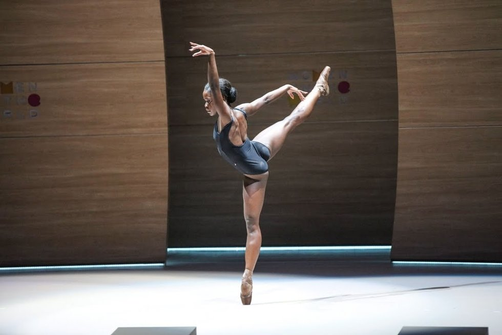 Michaela DePrince in arabesque on pointe in a black leotard, onstage with a wooden-looking backdrop. She faces away from the audience and her wrists are flared.