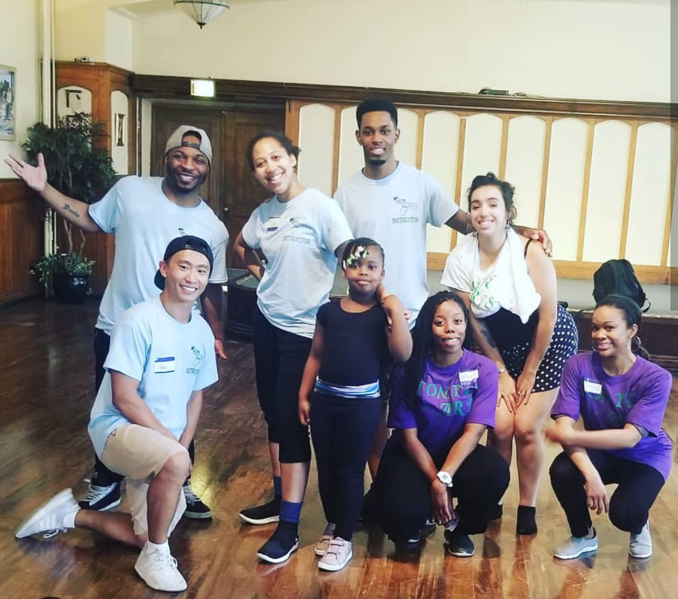 A group of dance teachers poses with a young black female student.