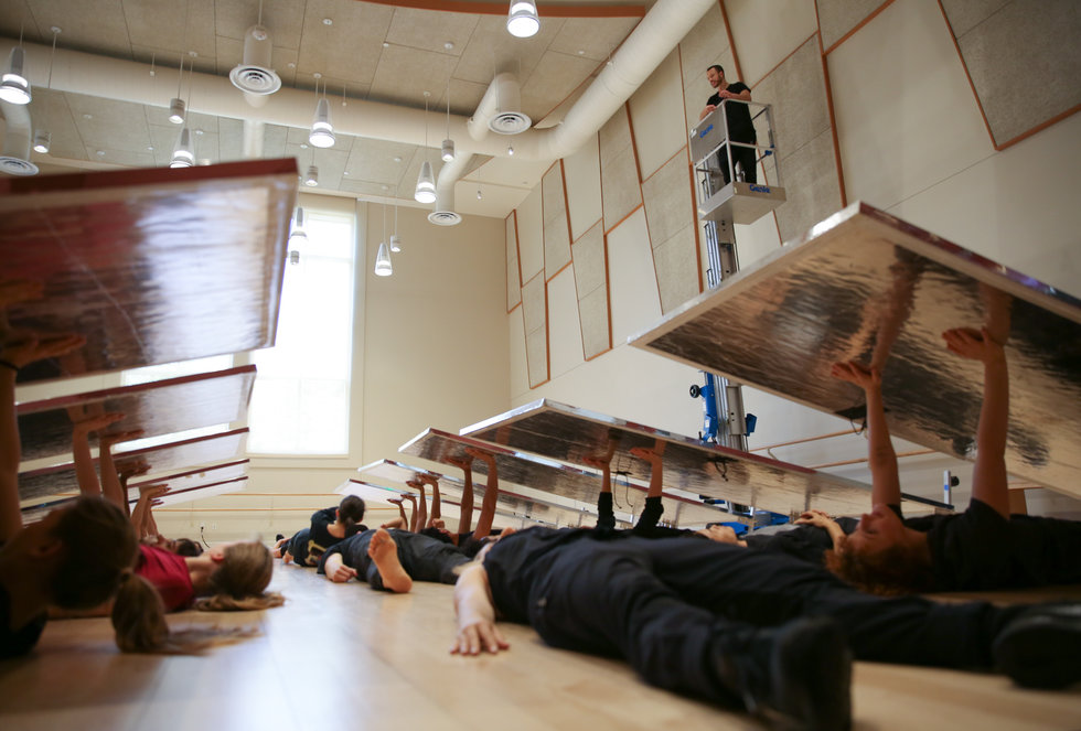 A group of dancers lies on the ground and pushes up planks of wood as Tony Testa looks over the formation from a cherry picker