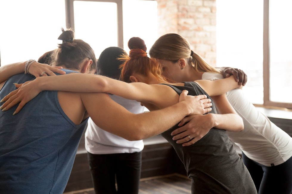 Dancers embrace each other in a group