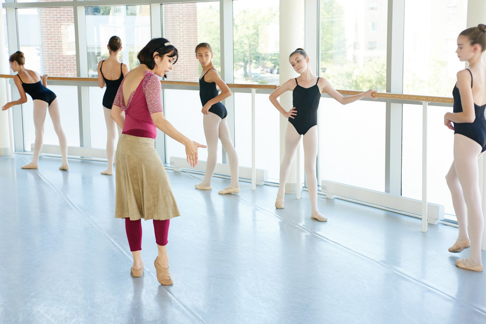Reyes, in a pink leotard and long beige skirt, demonstrates a foot exercise to a row of young girls standing at the barre. They are in a well-lit studio with large windows along the barre.