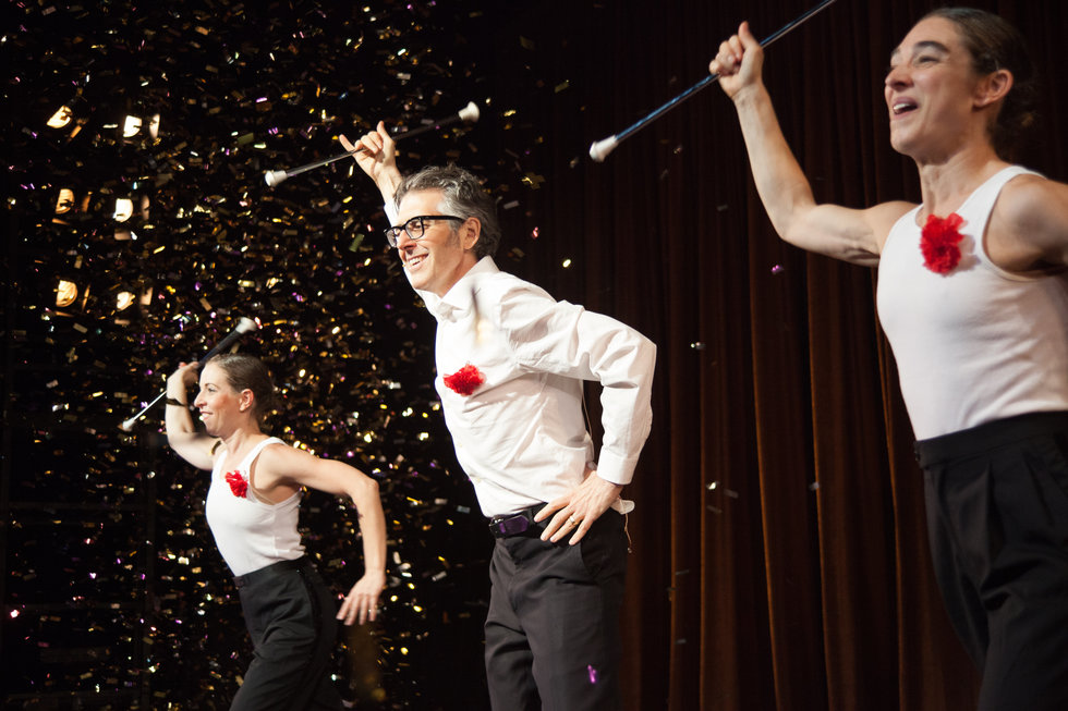 Barnes, Bass and Ira Glass performing together, they are all wearing white shirts with a red flower pinned on them and black pants. They each hold a baton in one hand which they are holding over head, with their other hand on their hip. Confetti rains down on them, and they are grinning.