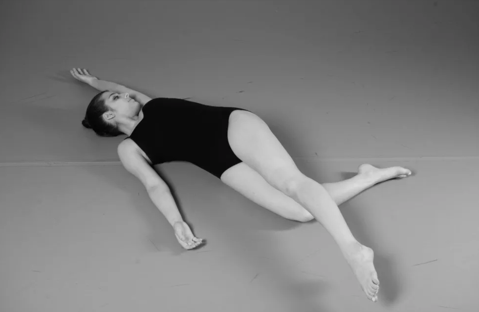 A dancer lies on the floor with one arm above her head and the leg on the same side reaching diagonally across her body.
