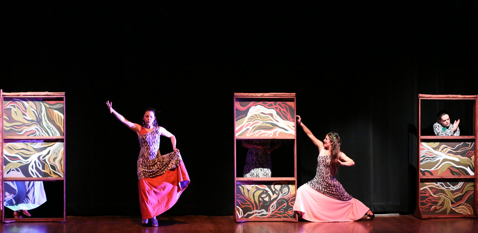 Three dancers on a stage with some set pieces that look almost like doors with colorful designs on them. The dancers wear different colorful costumes
