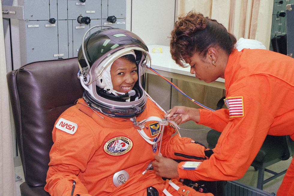 Jemison in a full astronaut suit, sitting in a chair while a technician runs some sort of test on her suit.