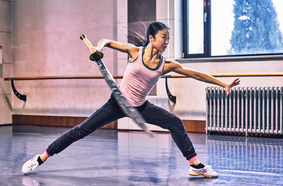 Chien-Pott in rehearsal holding a fake sword, lunging forward as if about to use it.