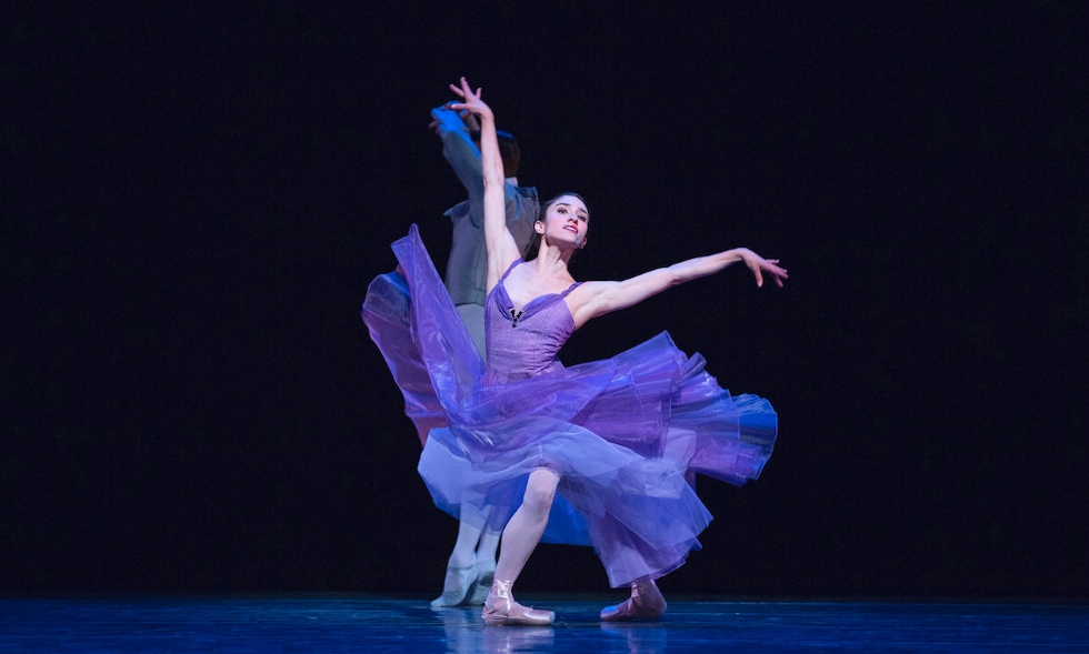 Biasucci onstage in a flowing purple dress, with the skirt floating around her as if she just landed from a jump or turn. She's in a long fourth position with her arms extended overhead.