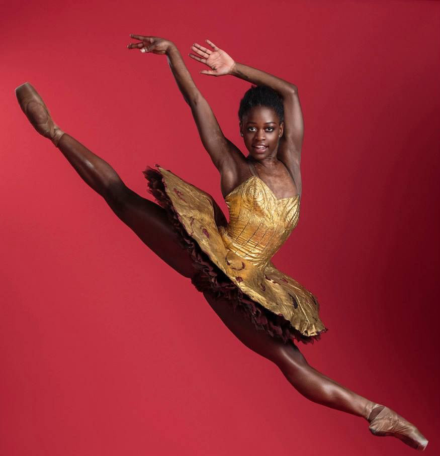 Michaela Deprince jumps against a red background at a photoshoot. She's wearing a gold costume with a classical tutu, her legs are straight and she looks directly at the camera, arms up and reaching behind her.