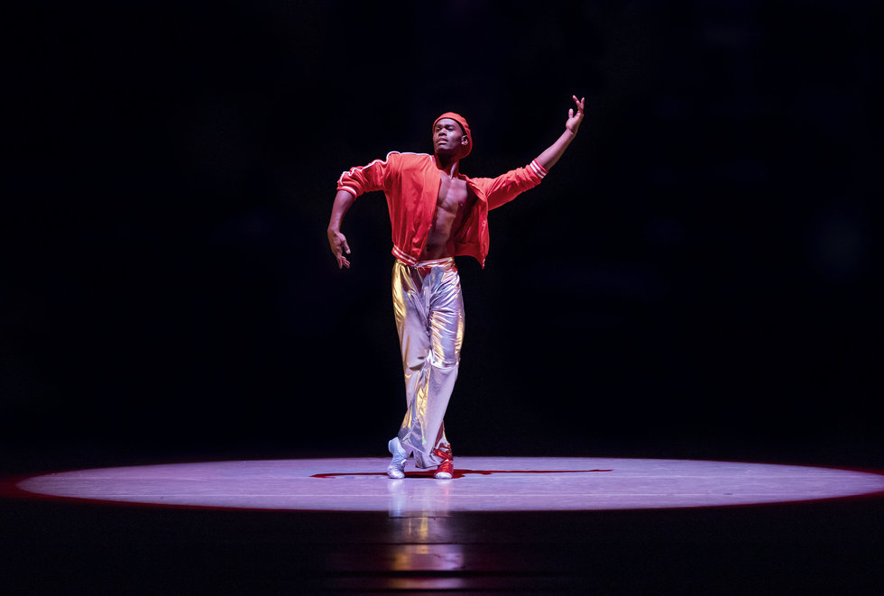 Jamar Roberts onstage dancing in a spotlight. He wears silver pants, an open red jacket, exposing his bare chest, and a red hat. He has one foot crossed in front of the other, one arm extended upward in a semi circle shape, the other one extended downward.