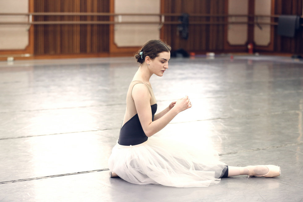 Womack in rehearsal in a studio, wearing a tan and blue leotard and a white romantic practice tutu. She kneels on the ground, her arms gesturing in front of her, eyes turned downward, as if rehearsing a dramatic moment.