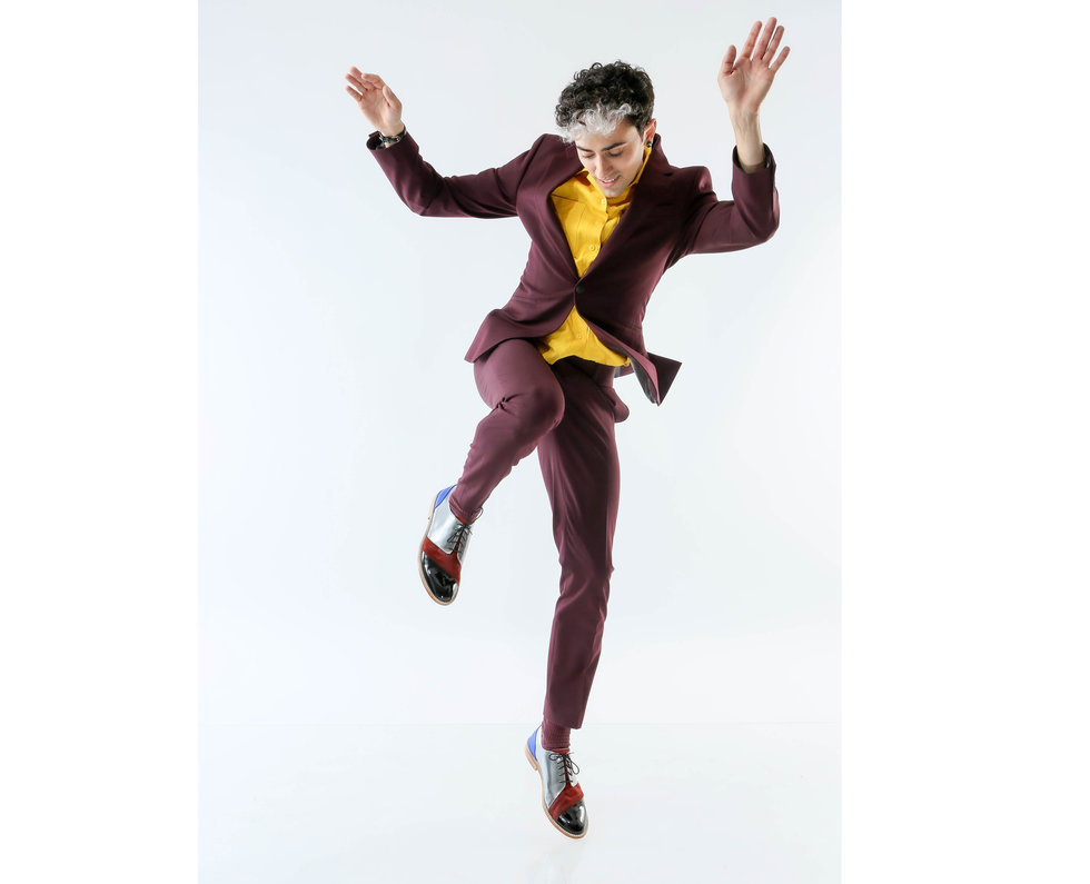 Teicher at a photoshoot in front of a light gray background, wearing a maroon suit, bright yellow shirt and silver, red and black tap shoes. He seems to be in the middle of a tap step, one leg raised in the air with the knee bent, arms casually flung in the air, looking down at his feet.