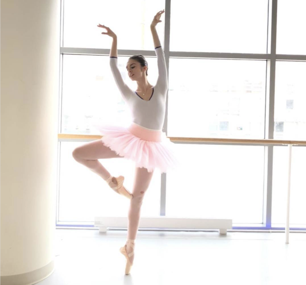 Valle stands on pointe with one leg in passe, arms reaching up and over her head with the backs of her wrists facing each other. She wears a white leotard and pink tutu, and stands in front of floor-to-ceiling windows.