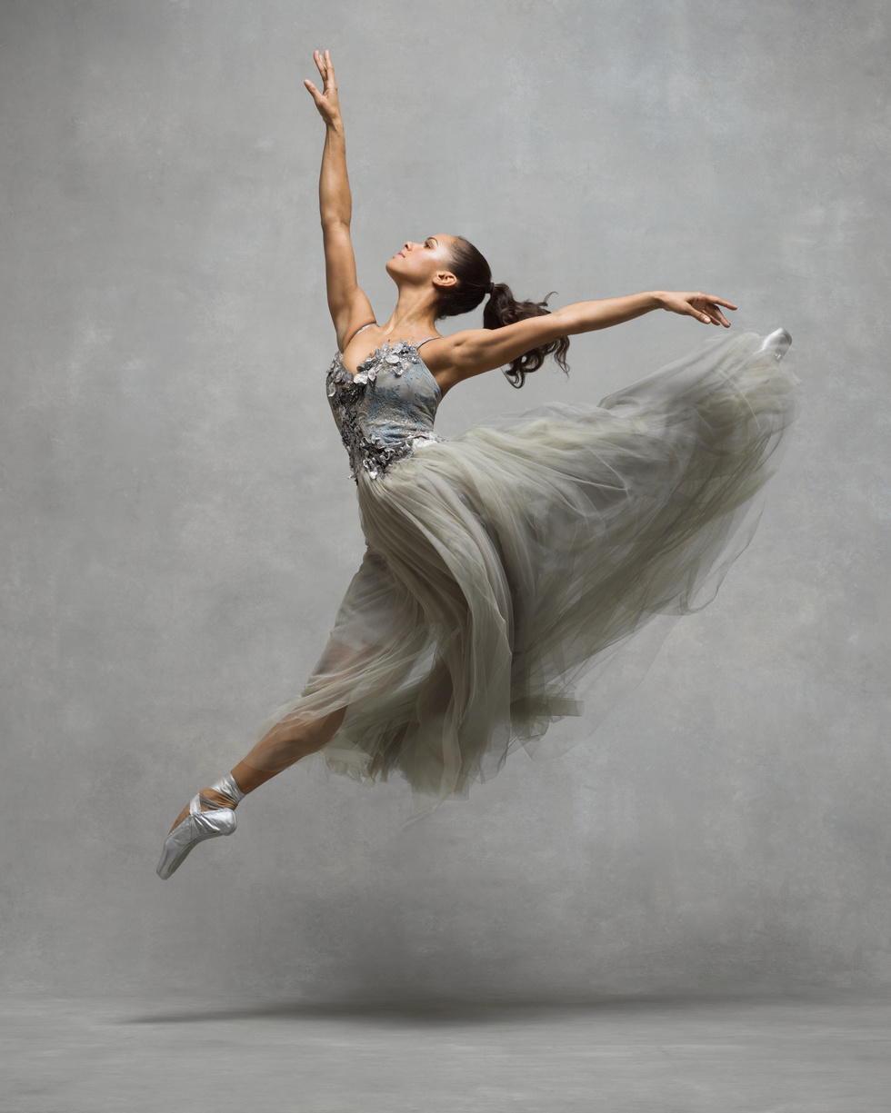 A female dancer jumps of the ground in profile, splitting her legs and looking towards a high front arm. She wears a long silver and gray gown and silver pointe shoes.