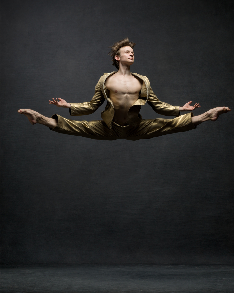 A male dancer is jumping high off the ground with split legs. He wears a gold vintage suit.