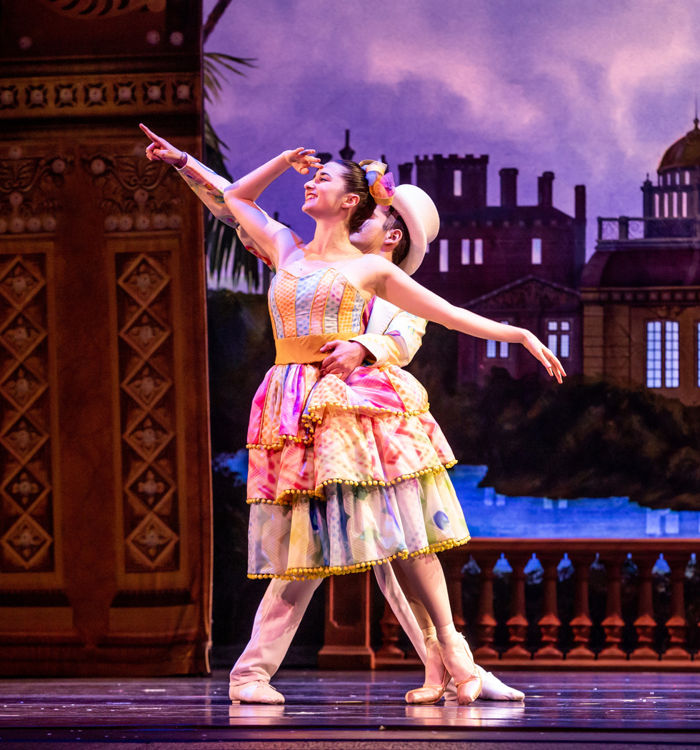 A male and female dancer pose close together. The woman is risingon pointe and wearing a pink, purple, yellow knee-length tutu. The man wears a white jacket and pants and has a top hat on.