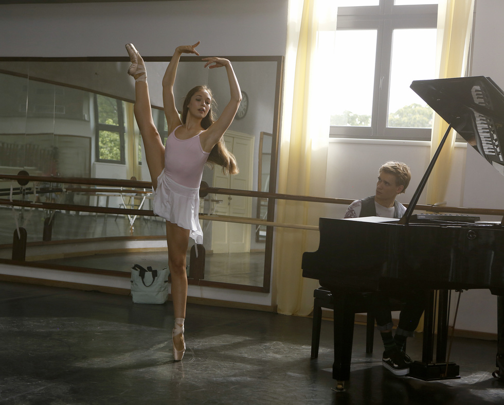 A ballerina balances on her left leg on pointe with her right leg lifted high to the side. A young man is to her left, playing the piano.