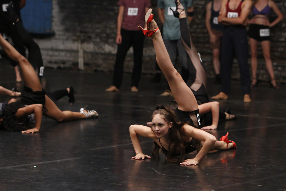 A young ballerina in shorts and high-heeled dance shoes auditions for a Broadway show. She is crouched on the floor with her weight on both hands, reaching her back leg behind her.
