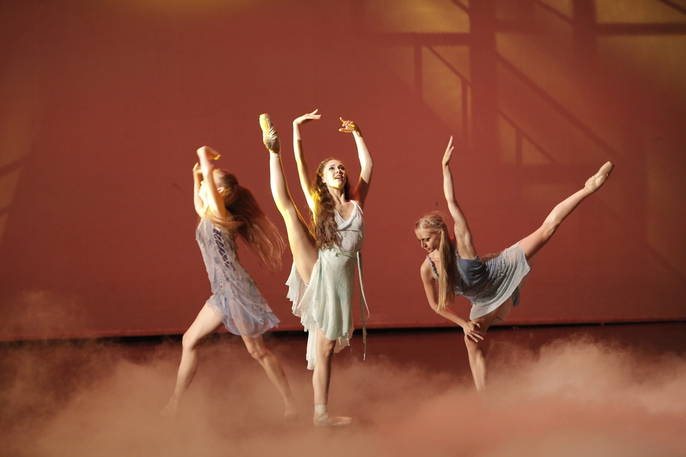 A young ballerina stands center stage, lifting her right leg high to the side and reaching both arms up in fifth position. A female dancer to her right is running past her and another dancer to her left is in arabesque.