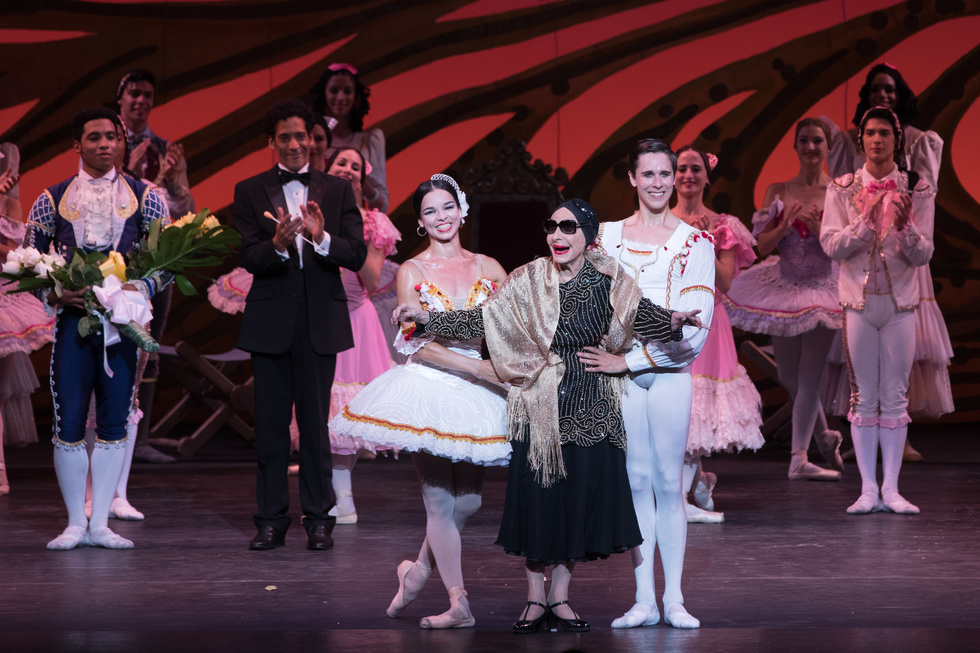 A bakkerina in a tutu, an onlder woman in sunglasses and a dark dress, and a male dancer in white tights and a white tunic, take a bow onstage.