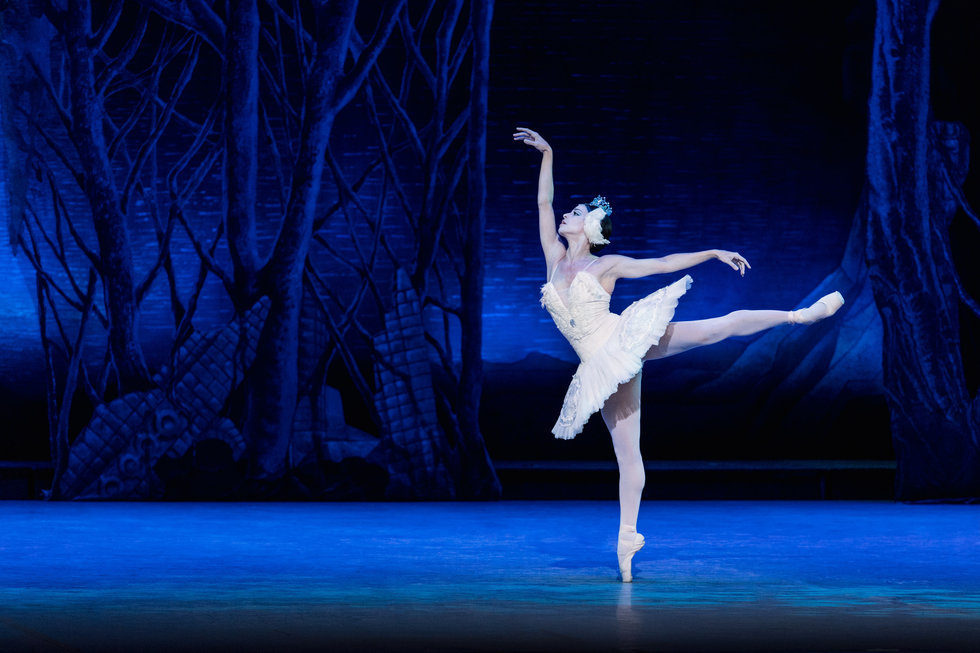 Vald\u00e9s, in the white tutu and headpiece typical for Swan Lake's white acts, balances in first arabesque on pointe.