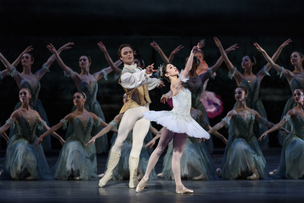 Yasmine Naghdi wearing a pale blue tutu stands in front of a group of women dressed in sheer blue dresses. She reaches towards the sky, standing in a back tendu. Behind her, Matthew Ball, dressed in white tights, a white shirt and a gold vest reaches towards her.