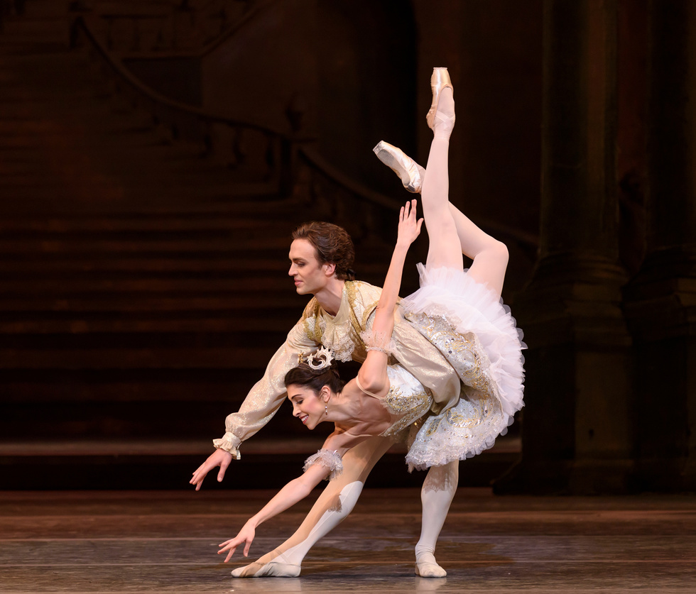 Yasmine and Naghdi are in a classic fish dive. They're both dressed in the Sleeping Beauty wedding attire. Naghdi wears a gold and white intricate tutu and Ball wears a gold vest, lace cravate and white tights.