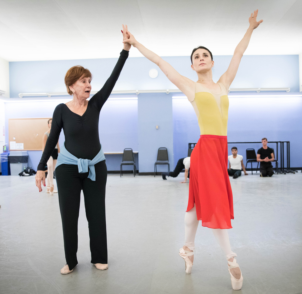 Sonia Calero-Alonso, wearing a black leotard and yoga pants, holds ballerina Sarah Lane's right hand as she balances on pointe.