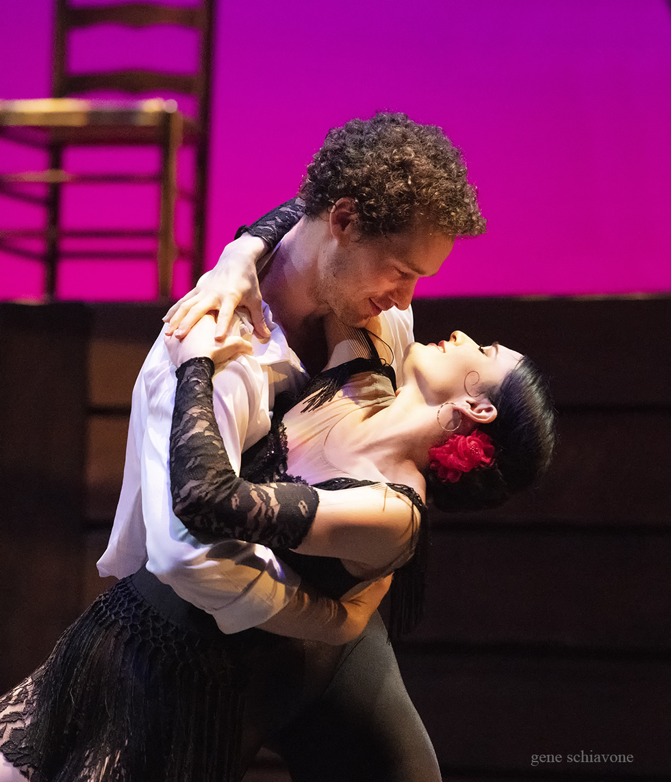Cory Stearns and Sarah Lane embrace onstage. Sarah wears a short, black, lacy dress and a rose in her hair.