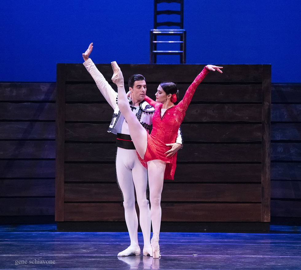 Sarah Lane, wearing a short red, lacy costume, kicks her right leg high in the air. Luis Ribagorda, wearing white tights and a white bolero jacket, holds on to her waist.