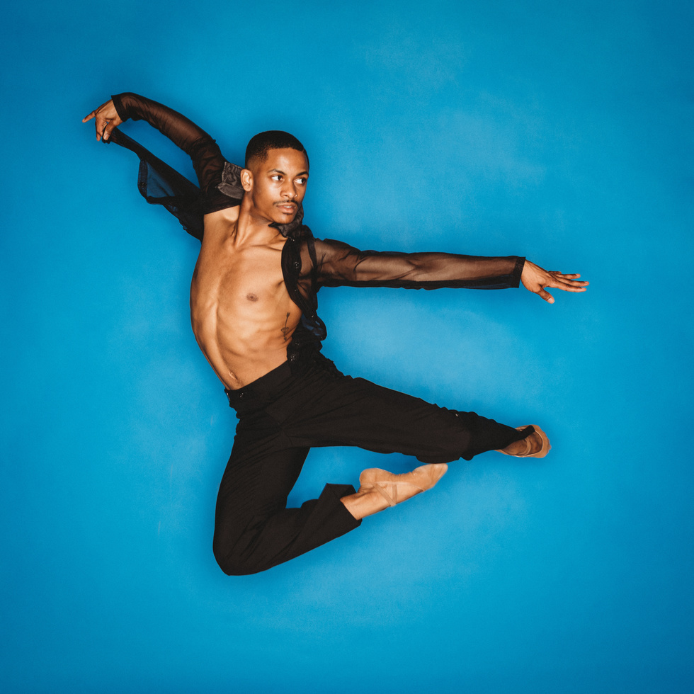 Roderick Phifer, dressed in black pants, ballet shoes and an open black, sheer shirt jumps in the air against a blue background.