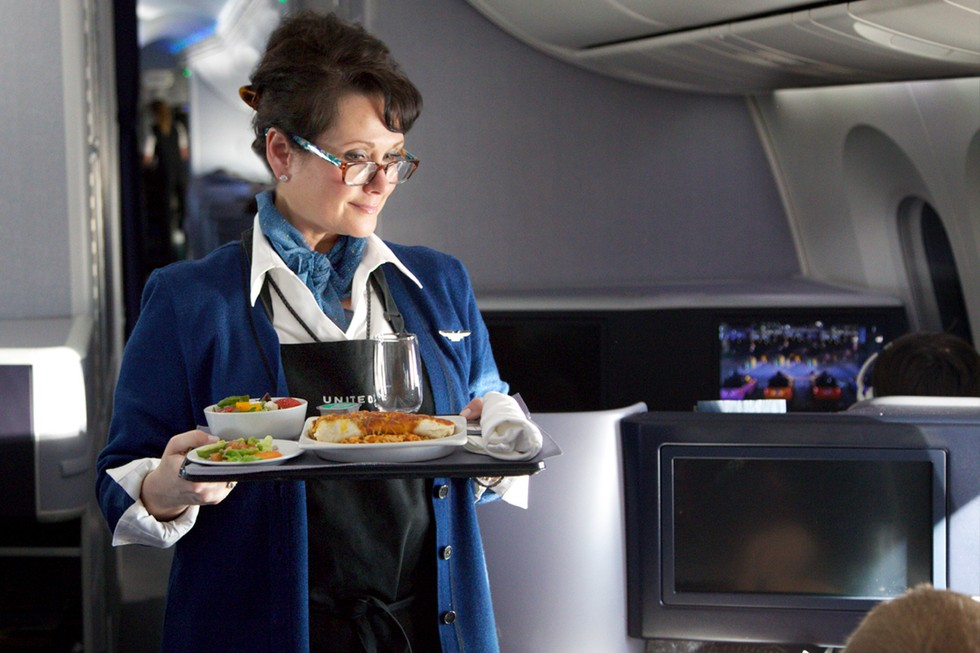 A United Flight Attendant Serves a Meal In Flight