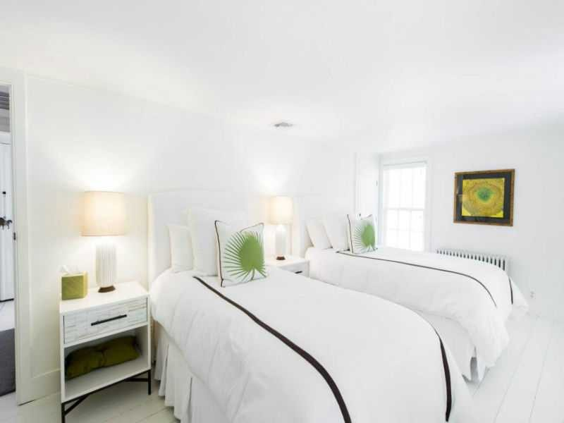 White bedroom with twin beds in Hamptons home of Luann de Lesepps of RHONYC