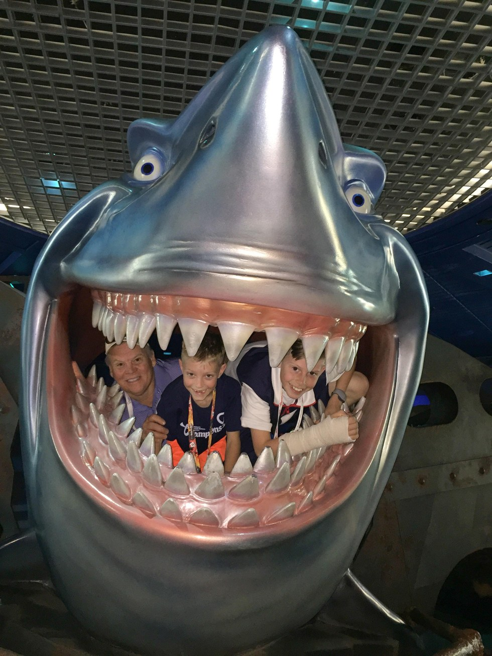 RE/MAX Senior Vice President Mike Reagan, Carson and his brother Tanner pose with a shark at Epcot Theme Park